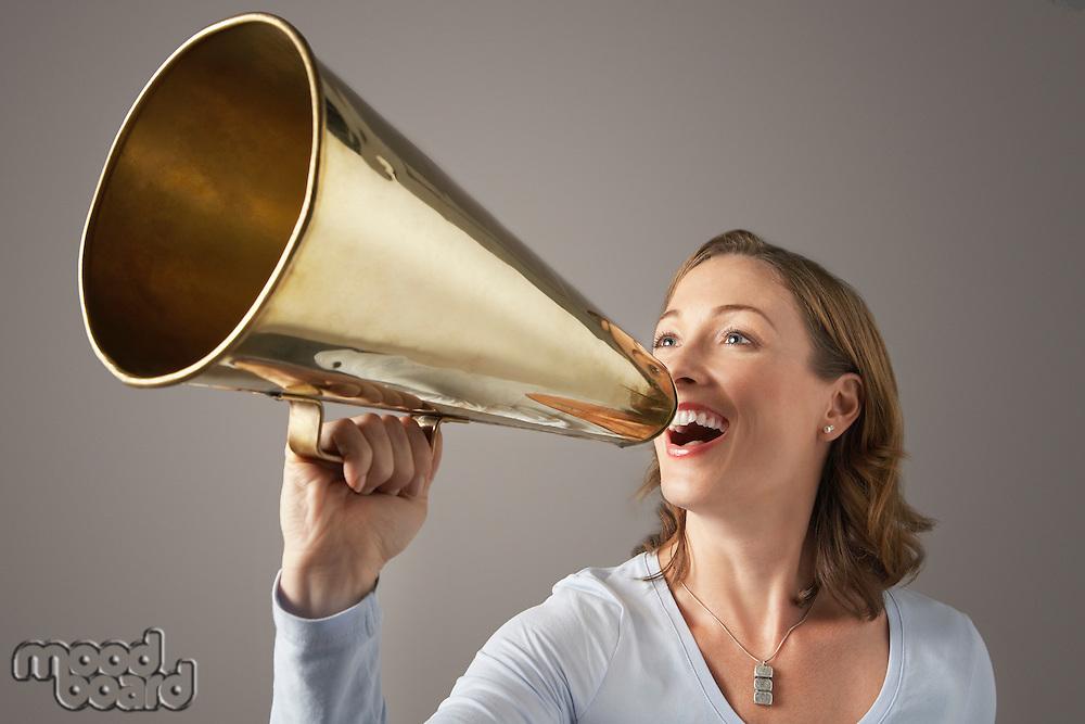 Smiling Mid-adult woman shouting through megaphone