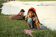 Young girls from the village of Beghrajpur, Muzaffarnagar District, Uttar Pradesh, India, are collecting grass for their family's buffaloes from the banks of a large drain originating from the Beghrajpur Industrial Complex, mainly composed of chemical factories, a few hundred meters upstream, on Sunday, Mar. 30, 2008. The white drain, completely covered in foam, will reach the Kali river (East) in Usampur Bhopara village. At the end of its journey, the watercourse will eventually join the largest Ganges river injecting a deadly dose of pollutants into its Holy waters.