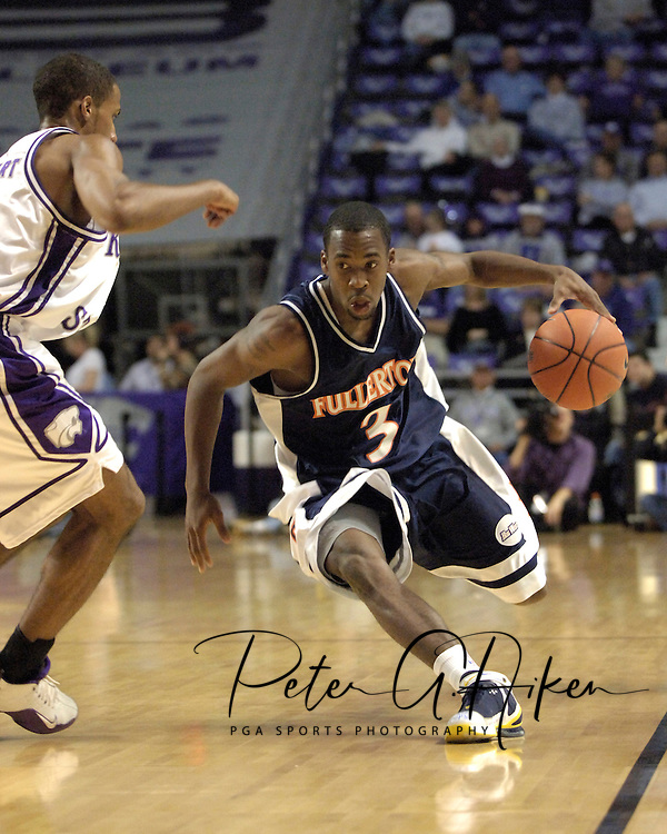 Cal State Fullerton guard Bobby Brown (R) dirves up the sideline against pressure from Kansas State guard Clent Stewart (L) during the first half at Bramlage Coliseum in Manhattan, Kansas, November 30, 2005.  K-State beat Titans of Cal State Fullerton 84-59.
