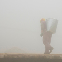 Woman carrier with heavy carriage walking in the fog