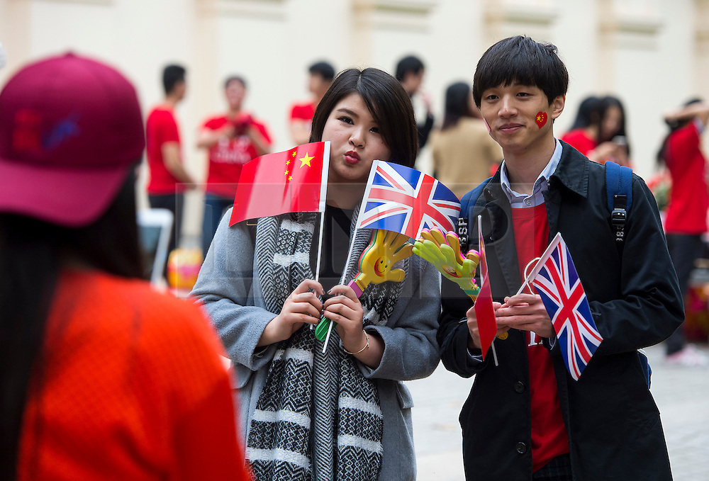 © Licensed to London News Pictures. 20/10/2015. London UK. Two chinese people pose for a photograph while holding union jack flags on The Mall in London leading to Buckingham palace as Chinese President Xi Jinping starts day one of a four day State Visit to the United Kingdom. Photo credit: Ben Cawthra/LNP