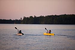 Two girls kayaking on Umbagog Lake at Umbagog Lake State Park, Cambridge, New Hampshire.