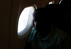 An African refugee looks out of a window on a plane heading to Paris from Malta July 5, 2010. A group of 93 African and Iraqi refugees were relocated to France on Monday as part of the intra-EU Relocation from Malta (EUREMA) pilot project, which aims to relocate refugees from Malta to other EU member states.<br />