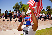 May 29 - PHOENIX, AZ: A man with a Mexican wrestling mask sells American flags at a pro-immigration march in Pheonix Saturday. More than 30,000 people, supporters of immigrants' rights and opposed to Arizona SB1070, marched through central Phoenix to the Arizona State Capitol Saturday. SB1070 makes it an Arizona state crime to be in the US illegally and requires that immigrants carry papers with them at all times and present to law enforcement when asked to. Critics of the law say it will lead to racial profiling, harassment of Hispanics and usurps the federal role in immigration enforcement. Supporters of the law say it merely brings Arizona law into line with existing federal laws.  Photo by Jack Kurtz / ZUMA Press