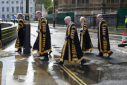 © Licensed to London News Pictures. 01/10/2019. London, UK. A Supreme Court Judge leaps over a puddle of rain water as Judges, QCs and senior legal figures arrive in The Houses of Parliament after attending the annual service to mark the start of the legal year. The start of the new legal year is marked with a traditional religious service in Westminster Abbey followed by a procession to The Houses of Parliament where the Lord Chancellor (Justice Secretary) hosts a reception.   Photo credit: Dinendra Haria/LNP