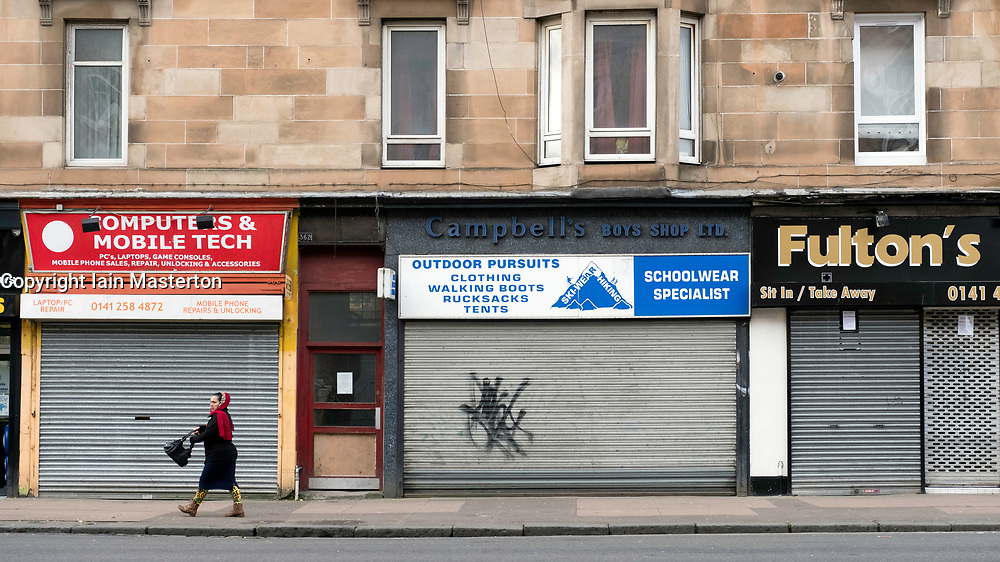 Closed shops with shutters down on Victoria Road in Govanhill district of Glasgow, Scotland, United Kingdom