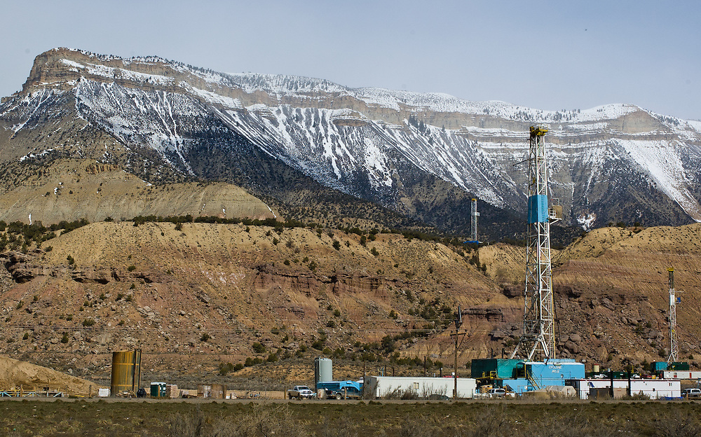 Gas exploration drilling rigs beneath the Roan Cliffs in the Piceance Creek Basin, Colorado