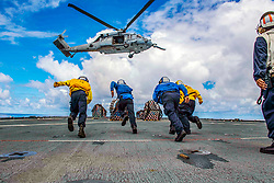 U.S. Sailors run to grab pallets off the flight deck of the amphibious dock landing ship USS Ashland (LSD 48) during a vertical replenishment (VERTREP) with the dry cargo and ammunition ship USNS Washington Chambers (T-AKE 11) in the East China Sea Sept. 22, 2018. The Ashland, part of the Wasp Amphibious Ready Group, with embarked 31st Marine Expeditionary Unit, is operating in the Indo-Pacific region to enhance interoperability with partners and serve as a ready-response force for any type of contingency. (U.S. Navy photo by Mass Communication Specialist 2nd Class Joshua Mortensen)