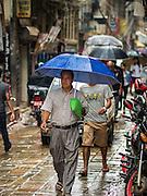 06 AUGUST 2015 - KATHMANDU, NEPAL: People walk down Sukra Path during a monsoon rain. It is a popular shopping street in Kathmandu.      PHOTO BY JACK KURTZ