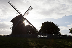 © Licensed to London News Pictures. 25/05/2015. Sandown, Isle of Wight, UK. The sun rises over Bembridge Windmill this morning, 25th May 2015. The windmill dates from c.1700 and is the last surviving windmill on the Isle of Wight, and is now kept by the National Trust. The weather is set to be generally dry, with cloud cover and localised sunny spells. Photo credit : Rob Arnold/LNP