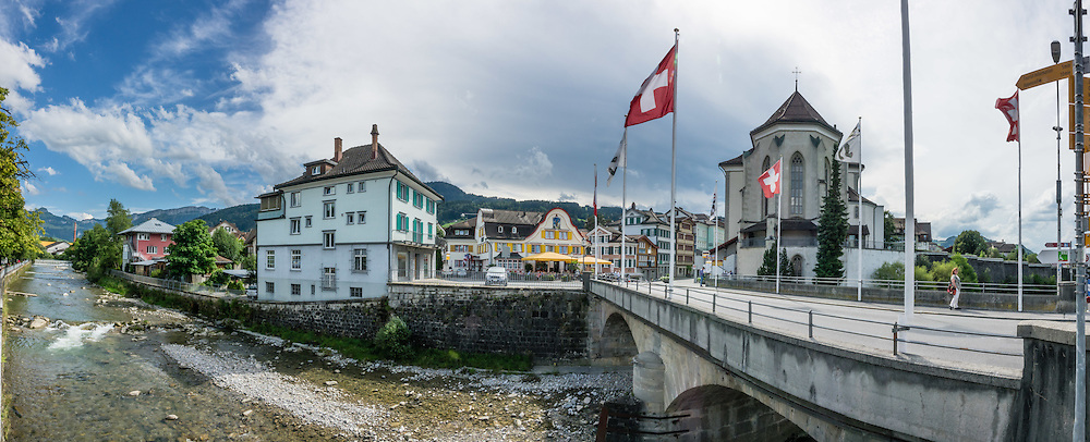 Adlerplatz is the heart of Appenzell village, in Switzerland, Europe. Appenzell's Roman Catholic St. Maurice (or Mauritius) parish church was built 1560–84. Metzibrücke bridge crosses Sitter river. Yellow shutters mark Hotel Cafe Adler. Most of the notable buildings in Appenzell were built in the 1500s. Appenzell Innerrhoden is Switzerland's most traditional and smallest-population canton (second smallest by area). This image was stitched from multiple overlapping photos.