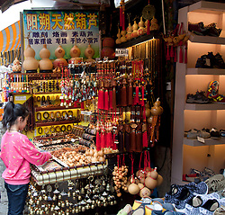 Young girl checks out the merchandise at a soluveneir shop on West Street, Yangshou. Yangshuo is a county and city under the jurisdiction of Guilin City, in the northeast of Guangxi Province, China. Its seat is located in Yangshuo Town. Surrounded by karst peaks and bordered on one side by the Li River it is easily accessible by bus or by boat from nearby Guilin. It is a major tourist and resort destination for Chinese and foreigners alike.