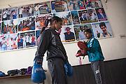 Deux jeunes filles prêtes à commencer une session de l'entraînement de boxe dans le gymnase de Bhiwani Boxing Club; derrière, les photos des personnes et moments importants pour l'école, qui a gagné une medaille de bronze aux Jeux Olympics de Pechin dans le 2008