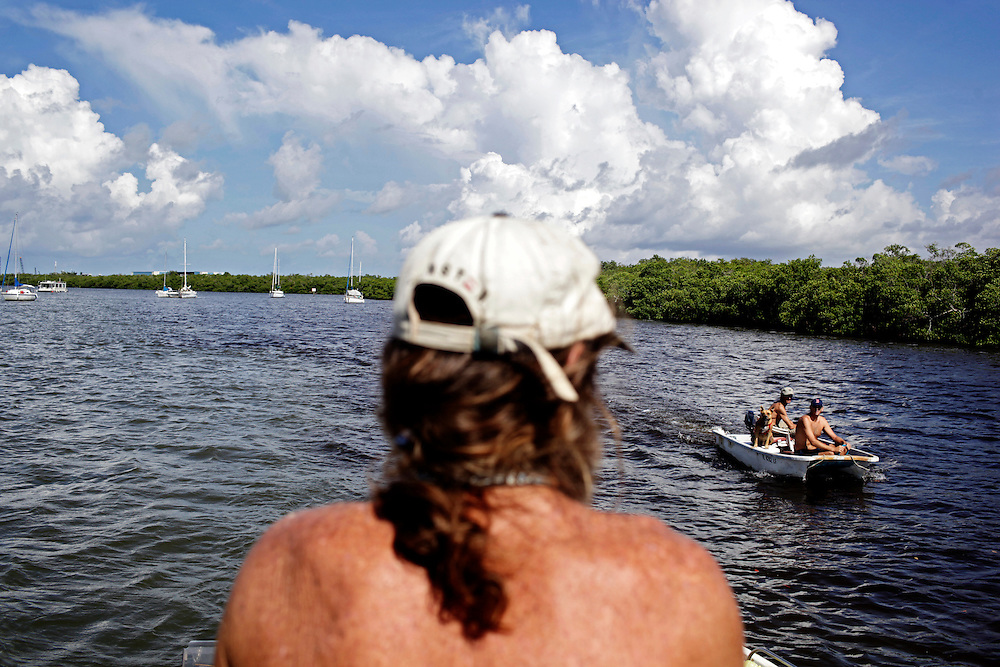 Randy Eibler, left, looks on as Kenny Canaday, center, Scot Janikula, right, and Janikula's dog Renegade, approach Eibler's houseboat on a skiff in Estero Bay, Fla. With few errands to run, visits from others living on their boats is common to help pass time.