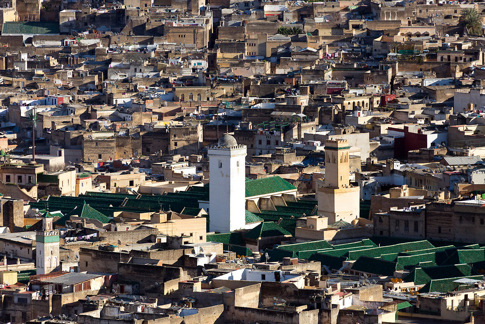 Al-Kairouine Mosque and University, Fez Medina, Morocco, 2018-02-03.<br /><br />View over the old Fez Medina and the Al-Karaouine Mosque and University (building with green tiled roof and white Minaret).<br /><br />Established at the very beginnings of Morocco's oldest imperial city, the University of Al-Karaouine (also written as Al-Quaraouiyine and Al-Qarawiyyin) was founded in 859 and is considered by Unesco and the Guinness Book of World Records to be the oldest continually operating university in the world.<br /><br />Located in the heart of the old city, the complex is composed of a mosque, university and library, and is connected to the labyrinth of interconnecting streets and alleyways on all four sides. Its ceramic green tiled roofs take centre stage over Fez's urban sprawl from any viewpoint over the city.