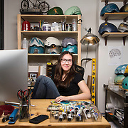 """February 24, 2014 - New York, NY : <br /> Danielle Baskin, founder of Belle Helmets, poses for a portrait in her office/studio space at 115 E. 23rd Street in Manhattan on Monday afternoon, Feb. 24. Danielle hand-paints bicycle helmets, which she sells to clients in New York and across the globe. Her setup includes a 21.5"""" iMac, visible at left, and an iPhone 5S, in foreground at center in an OtterBox case.  <br /> CREDIT: Karsten Moran for Macworld Magazin"""