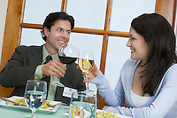 Young couple at restaurant table, toasting with wine