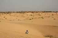 A boy in a desert dune looking at Timbuktu, Mali.