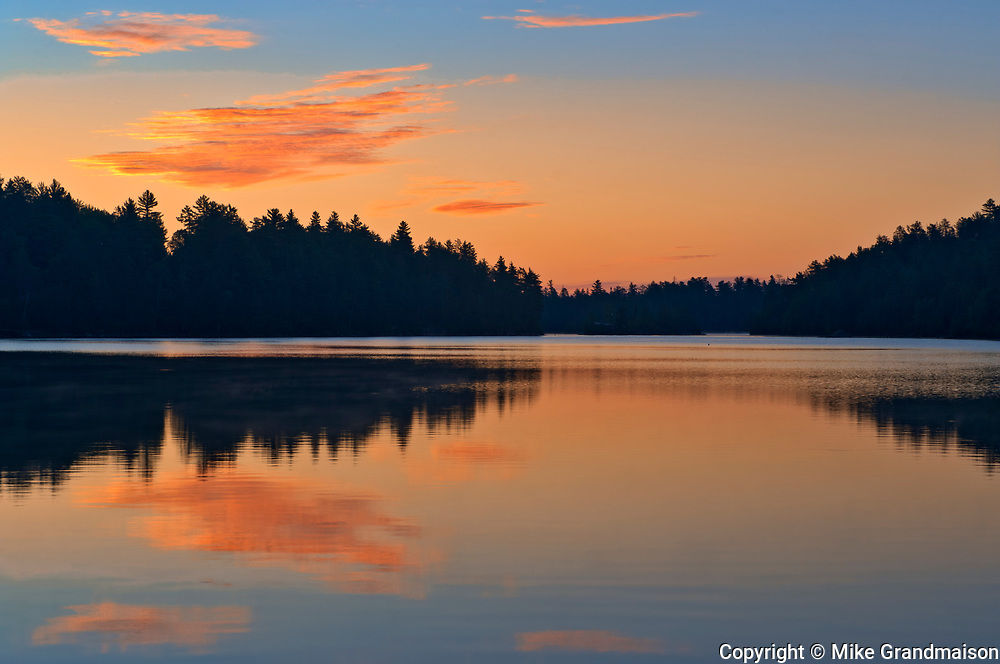 Clouds reflected in Snake Island Lake at sunrise. The White Bear Forest Conservation Reserve<br />