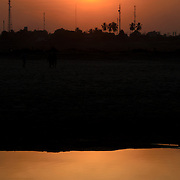 The setting sun over the Mekong River in Vientiane, Laos. Because the river marks the border, the trees and towers that are silhouetted on the far bank of the river are in Thailand. With copyspace.