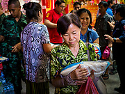 04 SEPTEMBER 2017 - BANGKOK, THAILAND: People pick up sacks of rice and bottles of cooking oil at Chaomae Thapthim Shrine. About 1,000 people came to the shrine for the annual food distribution. Staples, like rice and cooking oil, are donated to the shrine throughout the year and donated to poor people from the communities around the shrine. Food distributions like this are a tradition at Chinese shrines in Bangkok and a common way of making merit for the people who donate the staples.     PHOTO BY JACK KURTZ