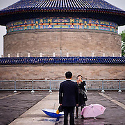 "Woman taking a photograph of her husband at ""The Temple of Heaven"" which is a complex of Taoist buildings situated in the southeastern part of central Beijing, China. #latergram #china #beijing #photography #couple #temple #umbrella #colors #past #camera"