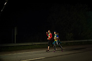 "Only 2 people run at 5:30 AM on the 20th Korrika. Murillo de las Limas  (Basque Country). April 1, 2017. The ""Korrika"" is a relay course, with a wooden baton that passes from hand to hand without interruption, organised every two years in a bid to promote the basque language. The Korrika runs over 11 days and 10 nights, crossing many Basque villages and cities. This year was the 20th edition and run more than 2500 Kilometres. Some people consider it an honour to carry the baton with the symbol of the Basques, ""buying"" kilometres to support Basque language teaching. (Gari Garaialde / Bostok Photo)"