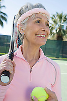 Senior woman holding tennis racket and balls