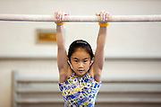 A small girl trains on the uneven bars in Beijing.