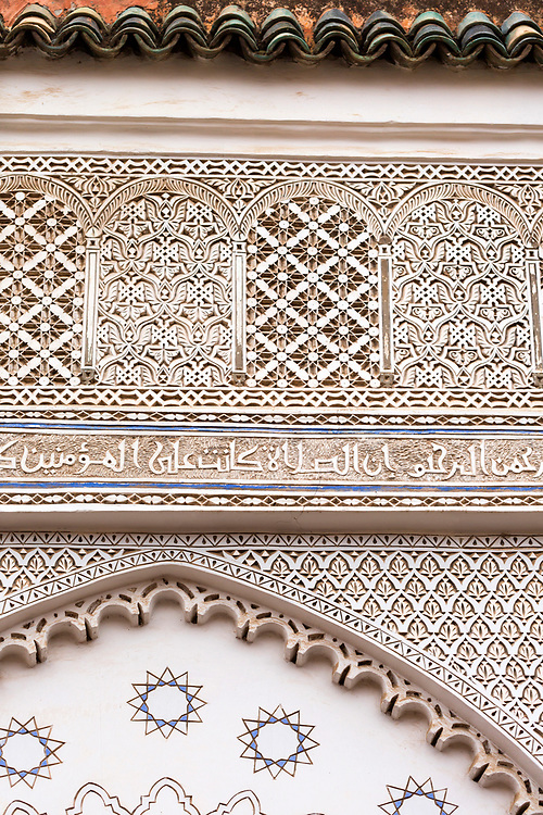 MARRAKESH, MOROCCO - 19TH APRIL 2016 - Close up of intricate and detailed stone carvings with Arabic scripture and geometric shapes lining the Sufi burial shrines of the seven sacred saints of Marrakesh, Morocco.