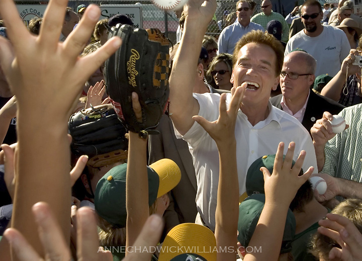 "Gov. Arnold Schwarzenegger hands out baseballs to Auburn little leaguers at Beggs Field in Auburn as he kicks off his ""Protecting the California Dream Tour"" on June 7, 2006."