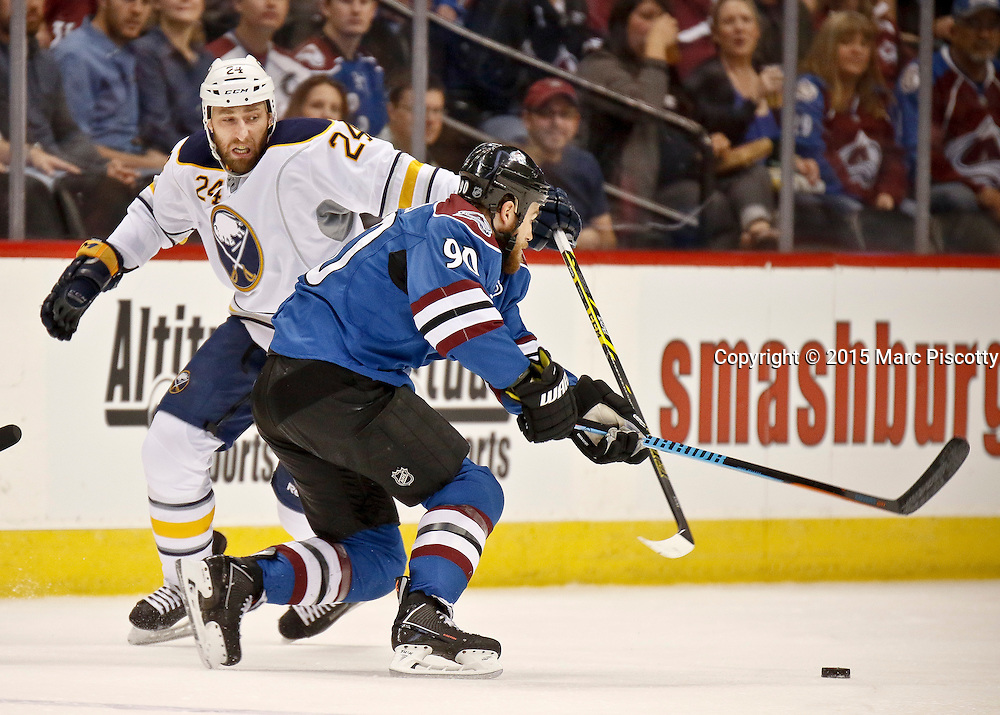 SHOT 3/28/15 7:18:28 PM - The Colorado Avalanche's Ryan O'Reilly #90 makes a move to get past the Buffalo Sabres' Tyson Strachan #24 during their regular season NHL game at the Pepsi Center in Denver, Co. The Avalanche won the game 5-3. (Photo by Marc Piscotty / © 2015)