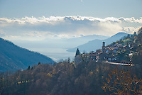 Ticino, Southern Switzerland. Looking towards the Lago Maggiore from the village of Maccagno, Italy.  The lake is shrouded in mist.