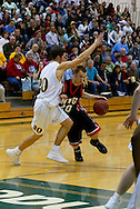 1/13/2006: Justin Parnell of the Northwest Nazarene University Crusaders drives past Freshman guard Trenton Millar (20) of the UAA Seawolves in the Alaska Anchorage comeback victory over Northwest Nazarene, 60-57, in men?s basketball action at the Wells Fargo Sports Complex on Saturday.