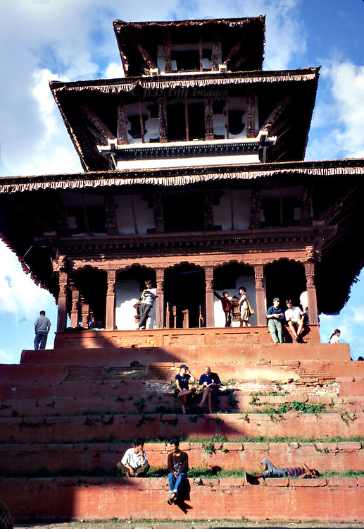 Young people lounging on the stepped platform of a Hindu temple in Patan, Kathmandu, Nepal.