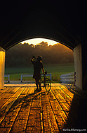 Road bicyclist takes water break at the Hogback Covered Bridge in Madison County, Iowa, USA model released