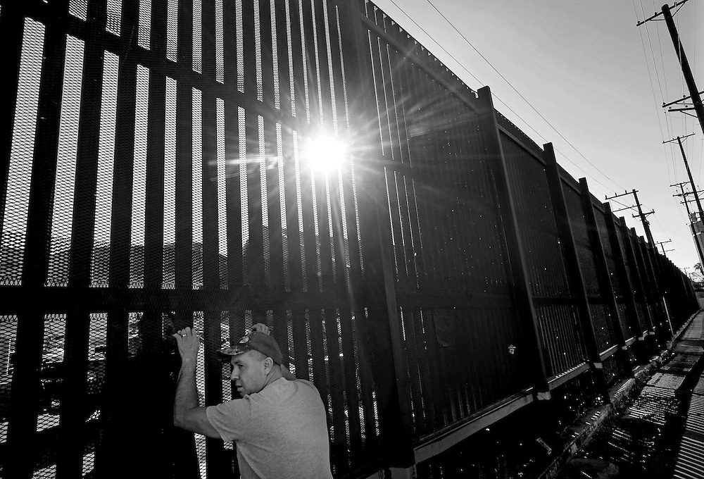 CALEXICO, CA-NOV 19: A man stands at the U.S. Mexico border wall in Calexico, CA on Wednesday, November 19, 2014. President Barack Obama plans to announce executive action on Immigration reform Thursday Evening.  As many as 5 Million undocumented immigrants could, on a temporary basis, be granted work permits and exempted from deporation.(Photo by Sandy Huffaker/Getty Images)