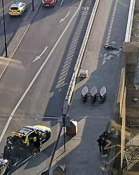 © Licensed to London News Pictures. 29/11/2019. London, UK. Armed police (foreground) train their guns on the body of a man (background) as it lies motionless on London Bridge after police shot the man following reports of a series of stabbings. Photo credit: LNP