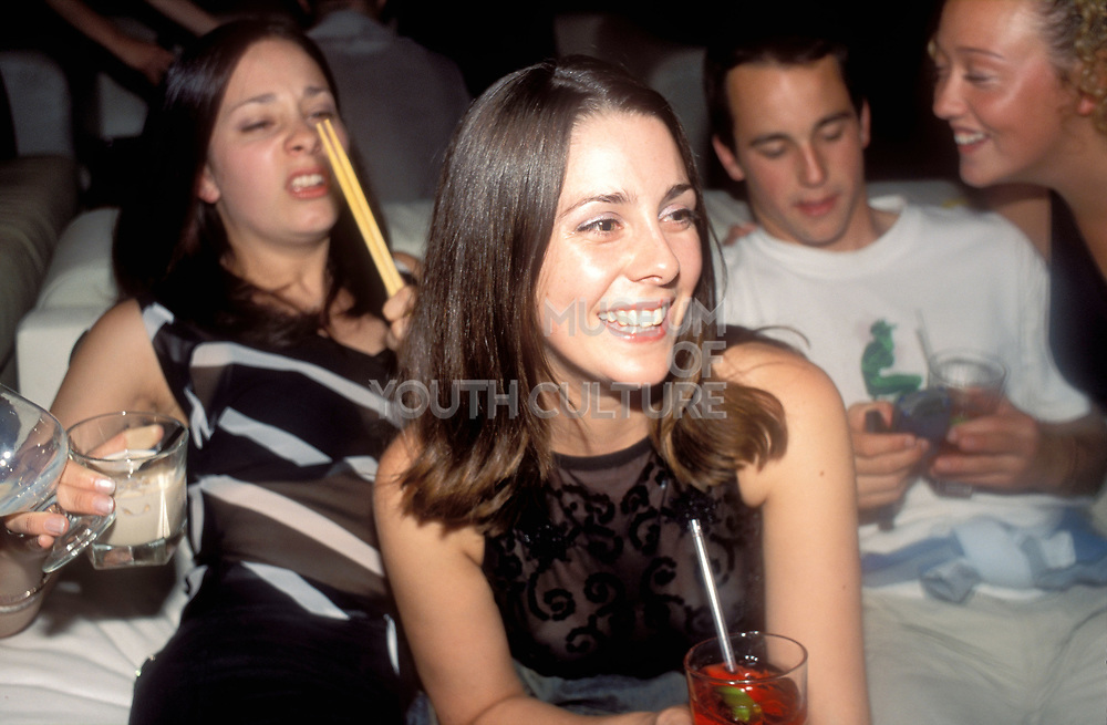 A smiling girl, sat down with friends, drinking in a bar, UK 2004<br />MODEL RELEASED