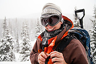 John Heisel smiles while touring to Peter Estin hut in a snow storm in Colorado. Telemark or AT skis with climbing skins are used to climb up steep snow slopes when doing backcountry skiing.
