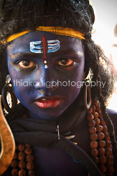 A young girl with blue face paint poses for a photo, Pushkar, India