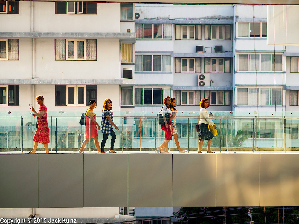 """27 MARCH 2015 - BANGKOK, THAILAND: Shoppers walk on a skywalk the connects two wings of """"EmQuartier,"""" a new mall in Bangkok. """"EmQuartier"""" is across Sukhumvit Rd from Emporium. Both malls have the same corporate owner, The Mall Group, which reportedly spent 20Billion Thai Baht  (about $600 million US) on the new mall and renovating the existing Emporium. EmQuartier and Emporium have about 450,000 square meters of retail, several hotels, numerous restaurants, movie theaters and the largest man made waterfall in Southeast Asia. EmQuartier celebrated its grand opening Friday, March 27.    PHOTO BY JACK KURTZ"""
