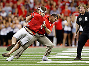 As security closes in, Ohio State strength and conditioning coach Anthony Schlegel tackles Anthony Wunder, a 21-year-old mechanical-engineering student at OSU, after he ran onto the field during the second quarter of the NCAA football game against the Cincinnati Bearcats at Ohio Stadium in Columbus on Sept. 27, 2014. Wunder was eventually arrested and charged with criminal trespassing.