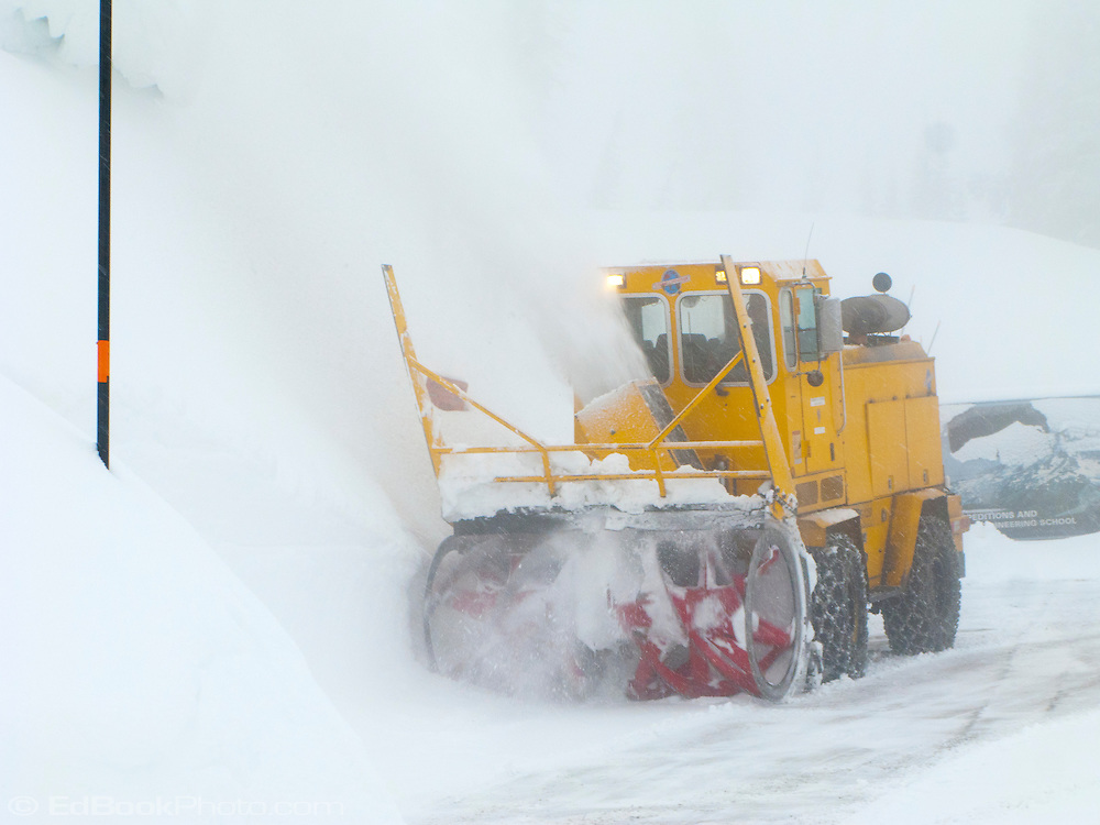 a snowblower is almost hidden from view by blowing snow and fog while clearing a road at Paradise in Mount Rainier National Park, in the Cascade Mountain Range, Washington, USA