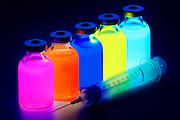 Syringe with vials of glowing fluid.Black light