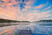 Dock and clouds reflection in Horseshoe Lake at sunrise<br />