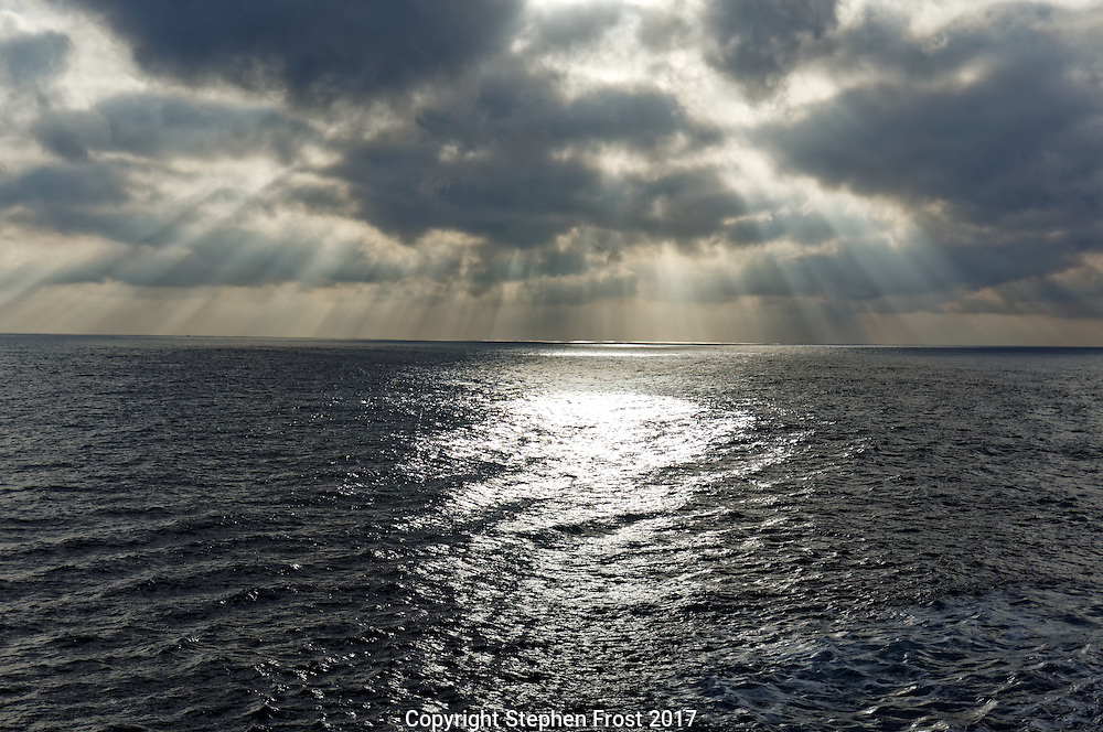 Crepuscular rays, also known as sunbeams, sun rays or god rays, shining through rain clouds over a stormy Atlantic.