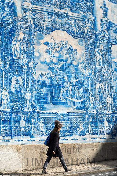 Young woman passing Azulejos Portuguese blue and white wall tiles of Capela das Almas de Santa Catarina  - St Catherine's Chapel in Porto, Portugal