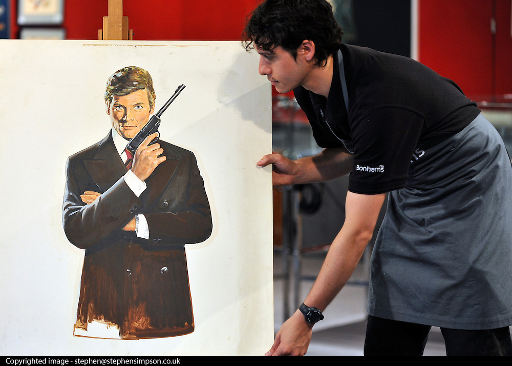 """© licensed to London News Pictures. LONDON, UK.  24/06/11. A Bonhams assistant holds a portrait of Roger Moore, attributed to Robert McGinnis. The artwork is believed to be the original for the poster of """"The Man with the Golden Gun"""". It is expected to raise £2000-3000. Photo call for highlights form Bonhams' upcoming Entertainment Memorabilia Sale. .Mandatory Credit Stephen Simpson/LNP"""