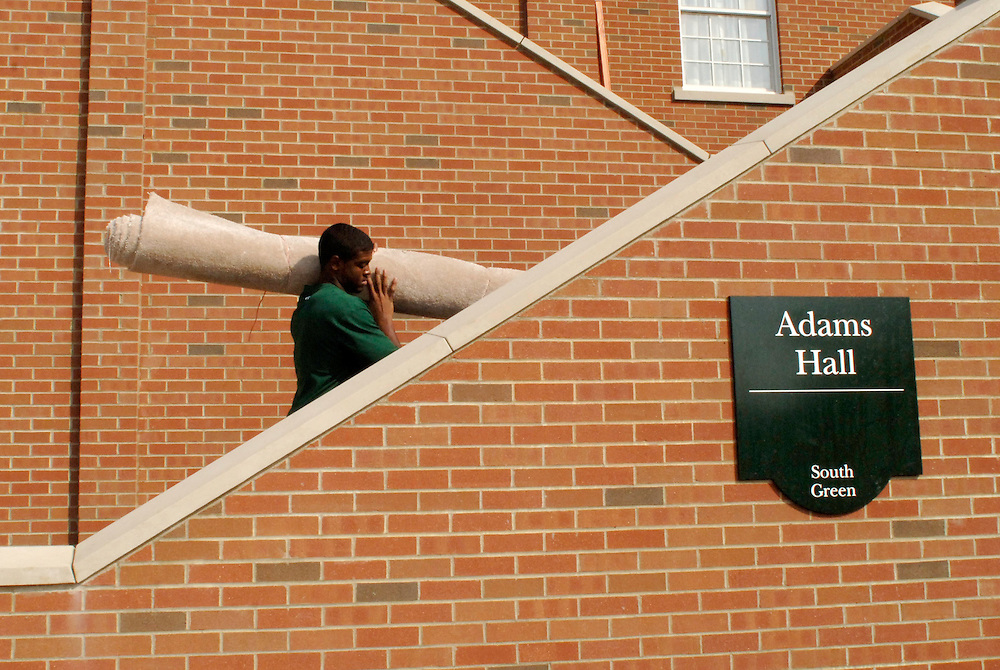 Ohio University junior Darnell Harris moves carpet into his new dorm room in Adams Hall on Sunday afternoon.